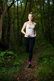 Beautiful young woman runs in forest - active runner running Royalty Free Stock Images