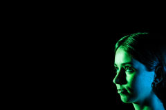 Beautiful young woman's face in blue and green lights at the cor Royalty Free Stock Photography