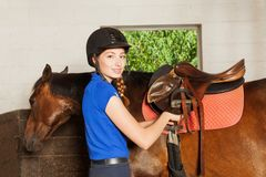Beautiful young woman saddling her bay horse Royalty Free Stock Photo