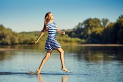 Beautiful young woman in sailor striped dress jamping Royalty Free Stock Photos
