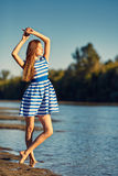 Beautiful young woman in sailor striped dress posing Stock Photography