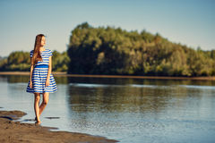 Beautiful young woman in sailor striped dress posing Stock Images