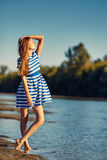 Beautiful young woman in sailor striped dress posing Royalty Free Stock Images