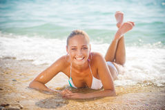Beautiful young woman on the sand on the seashore Royalty Free Stock Images