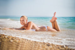 Beautiful young woman on the sand on the seashore Stock Photos