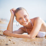 Beautiful young woman on the sand on the seashore Royalty Free Stock Photos