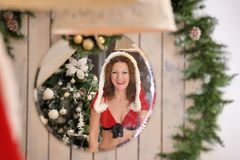 Beautiful young woman in Santa Claus clothes looking in the mirror Royalty Free Stock Images