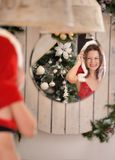 Beautiful young woman in Santa Claus clothes looking in the mirror Royalty Free Stock Photography
