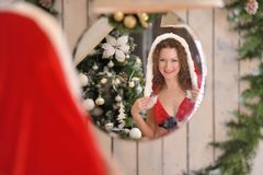 Beautiful young woman in Santa Claus clothes looking in the mirror Royalty Free Stock Image