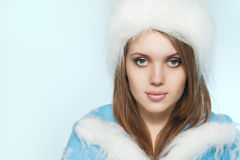 Beautiful young woman in Santa Claus clothes over blue backgroun Royalty Free Stock Image