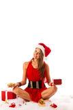 Beautiful young woman in santa claus dress sitting on the flor i Stock Images