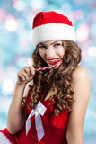 Beautiful young woman in a Santa Claus hat. Christmas portrait of a girl with a licorice candy Stock Photography