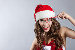 Beautiful young woman in a Santa Claus hat. Christmas portrait of a girl with a licorice candy Royalty Free Stock Photo