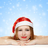 Beautiful young woman in santa claus hat laying on the table. On blue background with falling snowflakes Stock Photos