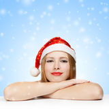Beautiful young woman in santa claus hat laying on the table. On blue background with falling snowflakes Stock Images