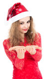 Beautiful young woman in Santa Claus hat looking at open hands Royalty Free Stock Photo