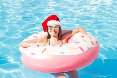 Beautiful young woman in Santa Claus hat with pink circle relaxing in blue swimming pool.  royalty free stock photos