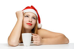 Beautiful young woman in santa claus hat siting at the table wit. H white cup isolated on white background Royalty Free Stock Photography