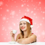 Beautiful young woman in santa claus hat siting at the table wit. H white cup on red background with falling snowflakes Stock Photos