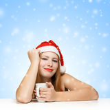 Beautiful young woman in santa claus hat sitting at the table wi. Th white cup on blue background with snowflakes Stock Photography