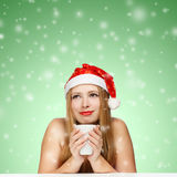 Beautiful young woman in santa claus hat sitting at the table wi. Th white cup on green background with falling snowflakes Stock Image