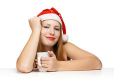 Beautiful young woman in santa claus hat sitting at the table wi. Th white cup on white background Royalty Free Stock Image