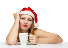 Beautiful young woman in santa claus hat sitting at the table wi. Th white cup on white background Stock Image