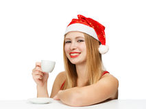 Beautiful young woman in santa claus hat sitting at the table wi. Th white cup on white background Royalty Free Stock Photo
