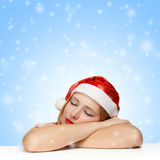 Beautiful young woman in santa claus hat sleeping on the table. On blue background with falling snowflakes Stock Photography