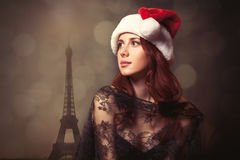 beautiful young woman in santa claus hat standing in front of wonderful eiffel tower background royalty free stock image