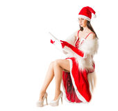 Beautiful young woman in Santa Clause costume holding Christmas present. Stock Photography