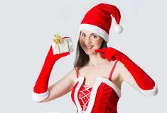 Beautiful young woman in Santa Clause costume holding Christmas present. Royalty Free Stock Image