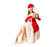 Beautiful young woman in Santa Clause costume holding Christmas present. Royalty Free Stock Photo