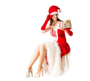 Beautiful young woman in Santa Clause costume holding Christmas present. Royalty Free Stock Photography