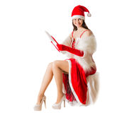 Beautiful young woman in Santa Clause costume holding Christmas present. Stock Image
