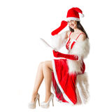 Beautiful young woman in Santa Clause costume reading the letter. Stock Images