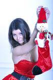 Beautiful young woman in Santa costume holds Christmas Sock Stock Image