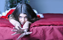 Beautiful young woman in Santa costume lies on bed Stock Photo