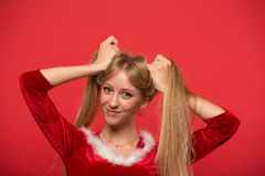 Beautiful young woman in Santa costume playing with a strand of her long silky hair, looking at camera on red background. Christmas Woman. Beauty Model Girl in Stock Images