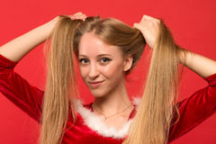 Beautiful young woman in Santa costume playing with a strand of her long silky hair, looking at camera on red background. Christmas Woman. Beauty Model Girl in Stock Photography