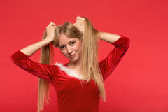 Beautiful young woman in Santa costume playing with a strand of her long silky hair, looking at camera on red background. Christmas Woman. Beauty Model Girl in Stock Image