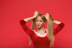 Beautiful young woman in Santa costume playing with a strand of her long silky hair, looking at camera on red background. Christmas Woman. Beauty Model Girl in Stock Photo