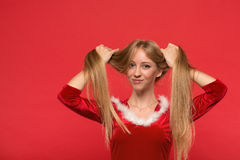 Beautiful young woman in Santa costume playing with a strand of her long silky hair, looking at camera on red background Stock Photos
