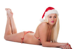 Beautiful young woman in a santa hat and  bikini posing. Stock Photography