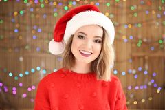 Beautiful young woman in Santa hat blurred lights background. Christmas celebration. Beautiful young woman in Santa hat on blurred lights background. Christmas Royalty Free Stock Photography