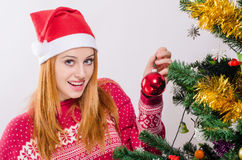 Beautiful young woman with Santa hat decorating the Christmas tree. Royalty Free Stock Images