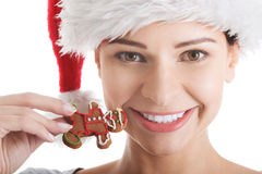 Beautiful young woman in santa hat eating gingerbread cookie. Stock Photography