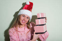 Beautiful young woman in Santa hat holding three Stock Photos