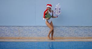 Beautiful young woman in Santa hat near swimming pool. Crazy beautiful young woman in Santa hat funny walking with present and Christmas tree by the swimming stock video footage