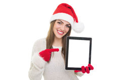 Beautiful young woman with Santa hat pointing at tablet screen Stock Photos